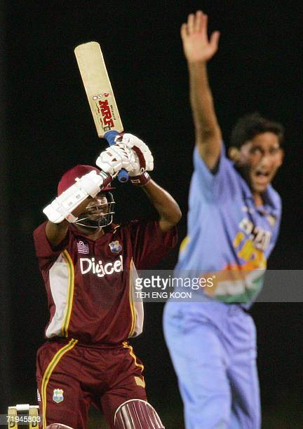 West Indian captain Brian Lara raises his bat while Indian pacer Ajit Agarkar raises his hands during a oneday match of the DLF triangular series in...
