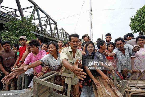 Flood victims crowd around in the mud as food packages are distributed in Kuala Simpang 30 December 2006 More than 250000 remaining evacuees from...