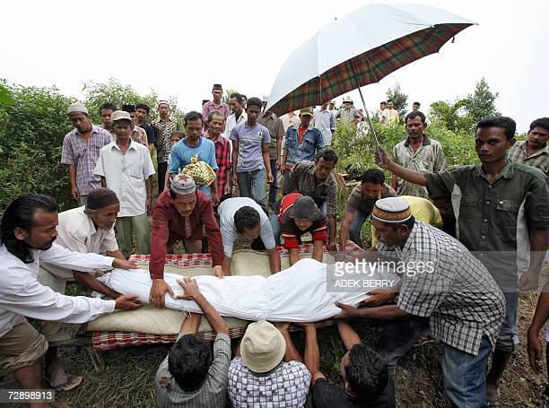 Villagers lower the body of Nur Bin Sulaiman one of the flood victims during a funeral in Benteng Anyer village in Manyak Payed Aceh Tamiyang 29...