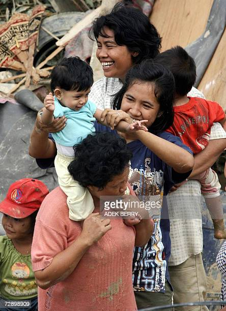 Women and children take a rest after their houses were swept away along the Tamiyang river in Kuala Simpang 29 December 2006 More than 250000...
