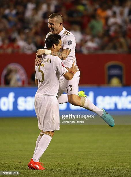 Kucka Juraj of AC Milan leaps on teammate Bonaventura Giacomo in celebration after defeating FC Bayern Munich in a friendly match in the...
