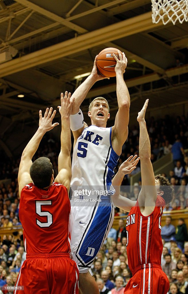 J.P. Kuhlman #5 of the Davidson Wildcats tries to stop Mason Plumlee #5 of the Duke Blue Devils as he drives to the basket during their game at Cameron Indoor Stadium on November 18, 2011 in Durham, North Carolina.