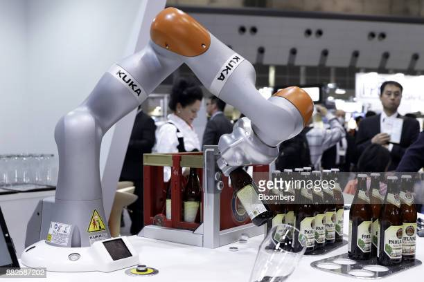 A Kuka AG LBR iiwa robotic arm opens a bottle of beer during a demonstration at the International Robot Exhibition in Tokyo Japan on Wednesday Nov 29...
