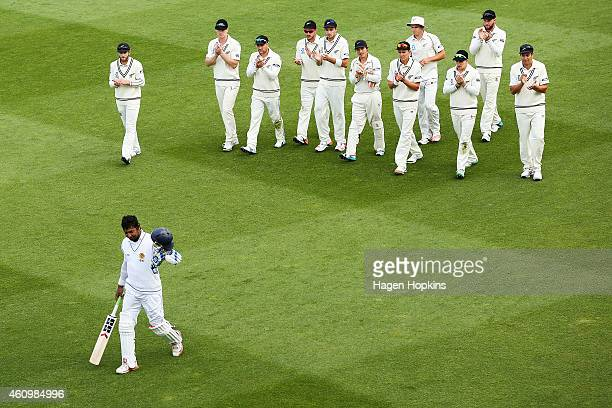 Kumar Sangakkara of Sri Lanka is applauded by New Zealand players as he leaves the field at the end of play after surpassing 12000 test runs during...
