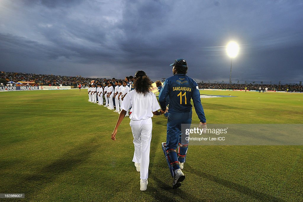 <a gi-track='captionPersonalityLinkClicked' href=/galleries/search?phrase=Kumar+Sangakkara&family=editorial&specificpeople=206804 ng-click='$event.stopPropagation()'>Kumar Sangakkara</a> of Sri Lanka walks out onto the field with his Player Escort during the ICC World Twenty20 2012 Group C match between Sri Lanka and South Africa at Mahinda Rajapaksa International Cricket Stadium on September 22, 2012 in Hambantota, Sri Lanka.