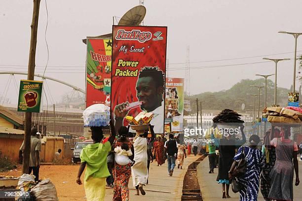 Kumasi people pass an advertisment featuring Michael Essien around Kumasi town' streets February 7 2008 in Kumasi Ghana