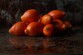 Close up view of a pile of kumquats. Dark, rustic copy space.