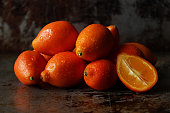 Close up view of a pile of kumquats with one sliced. Copy space.