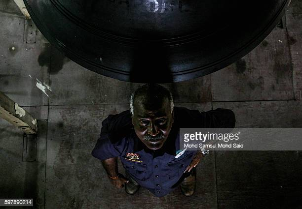 V Kunasegaran 60 pose fora photograph after he finished cleaning up the 118yearold giant bell manufactured in England inside the Sultan Abdul Samad...