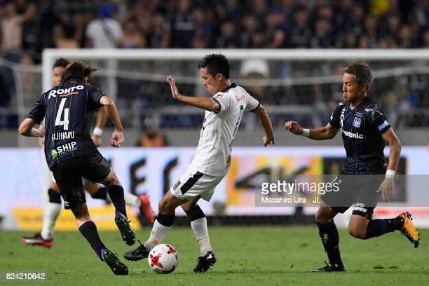 Kunimitsu Sekiguchi of Cerezo Osaka controls the ball under pressure of Hiroki Fujiharu and Yosuke Ideguchi of Gamba Osaka during the JLeague J1...