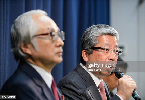 Kunio Yokoyama president and chief executive officer of Japan Post Co right speaks as Masatsugu Nagato president and chief executive officer of Japan...