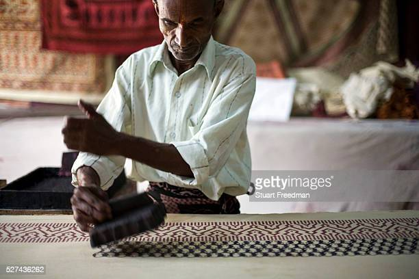Kunj Bihari Darbar a master printer prints on fabric using wooden blocks at a factory in Sanganer Jaipur India