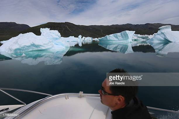 Kunuk Nielsen navigates his boat among calved icebergs from the nearby Twin Glaciers on July 31 2013 in Qaqortoq Greenland Boats are a crucial mode...
