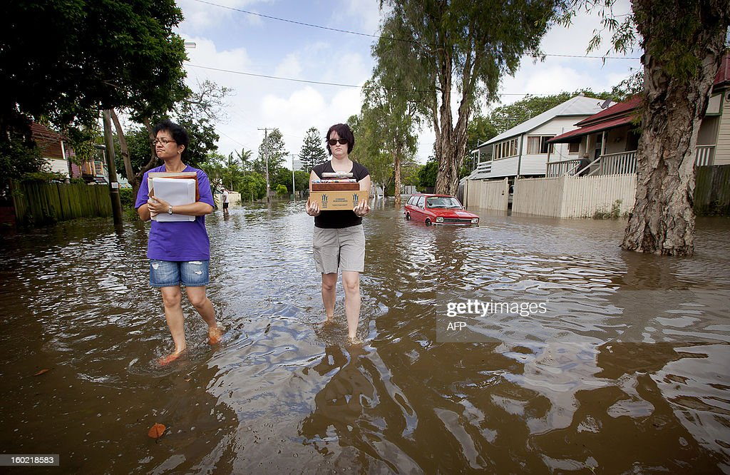 Kura Stainton (L) and Laura Hall (R) carry photographs from their flooded home in the inner Brisbane suburb of Newmarket on January 28, 2013 as high winds and heavy rains brought by ex-tropical cyclone Oswald have hit the state of Queensland. Helicopters plucked dozens of stranded Australians to safety in dramatic rooftop rescues on January 28 as severe floods swept the northeast, killing three people and inundating thousands of homes. AFP PHOTO / Patrick HAMILTON