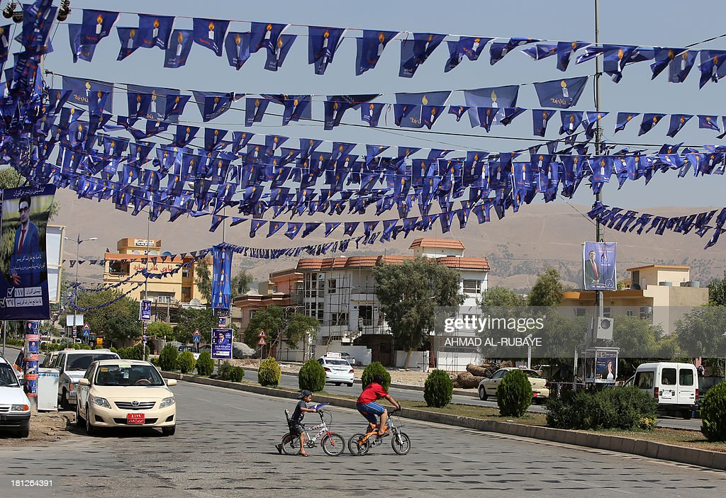 RAO Kurd young boy cross a street under blue flags emblazoned with a candle of the Movement for Change displayed in the streets as part ot the...