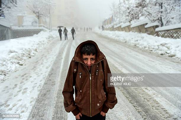 A Kurdish boy protects himself against the cold as heavy snow fall hits the city of Sirnak southeastern Turkey on January 1 2016 Tensions are running...