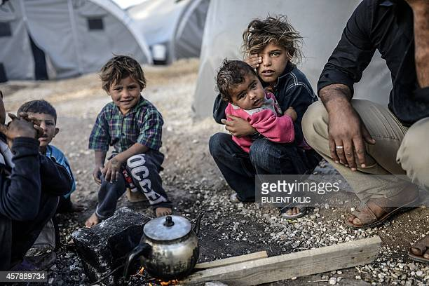Kurdish children sit around a fire outside a tent in the Rojava refugee camp in Suruc Sanliurfa province near the besieged Syrian town of Kobane also...