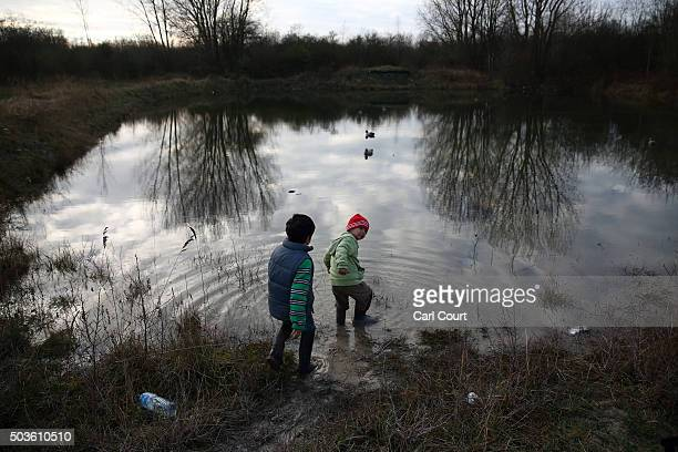 Kurdish children wade in a lake near a new migrant camp on January 6 2016 in Dunkirk France Thousands of migrants continue to live in makeshift camps...