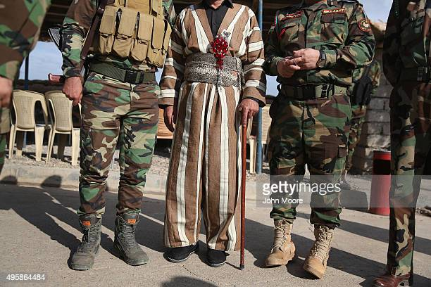 Kurdish civilian poses for photos with Kurdish Peshmerga troops on November 5 2015 near the frontline with ISIS fighters in Telskuf northern Iraq His...