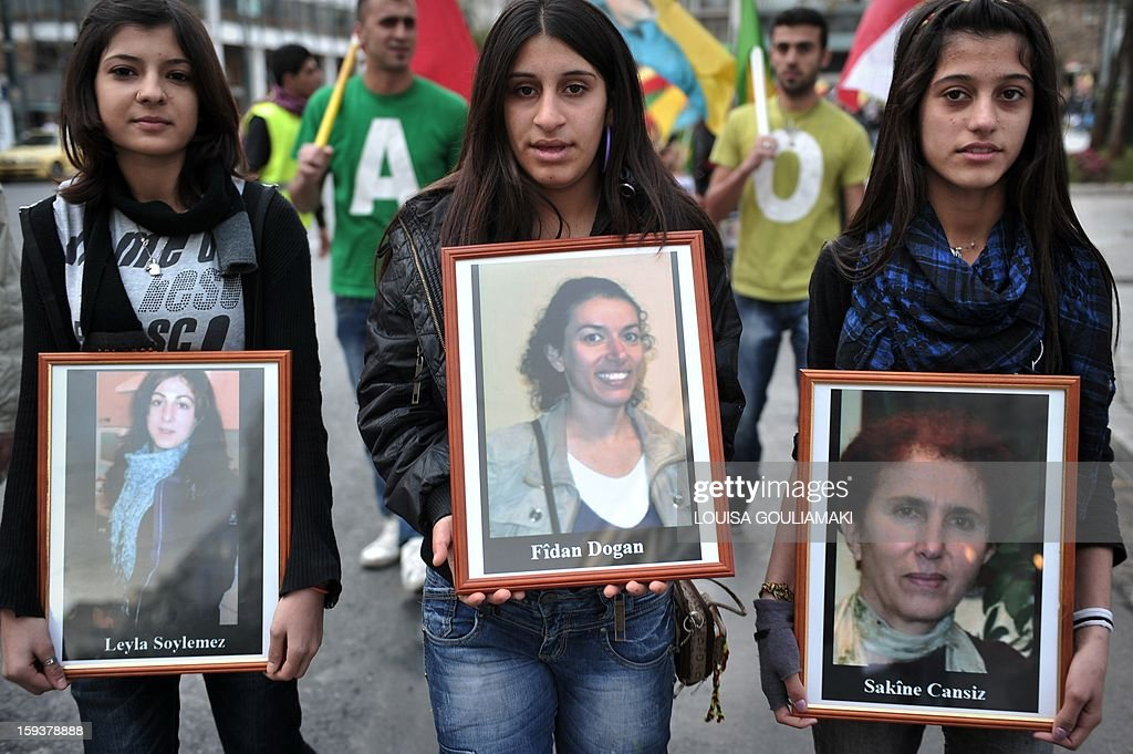 Kurdish demonstrators hold pictures of the three Kurdish activits found shot dead at the Kurdistan Information Bureau in Paris, during a protest in Athens by Kurds living in Greece on January 12, 2013. Kurdish activists have accused Turkey or rogue nationalist elements in the country's military of being behind the killings. AFP PHOTO / LOUISA GOULIAMAKI