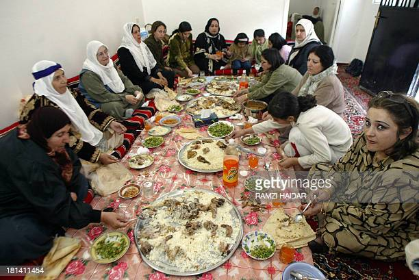 A Kurdish family sit to a dinner at home to celebrate the ancient Zoroastrian feast of Nowrus or New Year 1383 according to the solar calendar in...