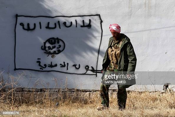A Kurdish fighter walks by a wall bearing a drawing of the flag of the Islamic State group in the northern Iraqi town of Sinjar in the Nineveh...