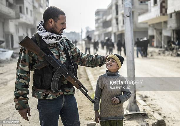 A Kurdish fighter walks with his child in the center of the Syrian border town of Kobane known as Ain alArab on January 28 2015 Kurdish forces...