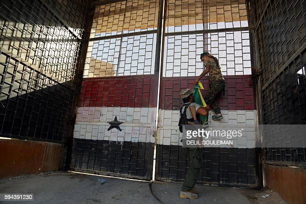 TOPSHOT Kurdish fighters belonging to the People's Protection Units put a YPG flag on the door of the central prison in the northeastern Syrian city...