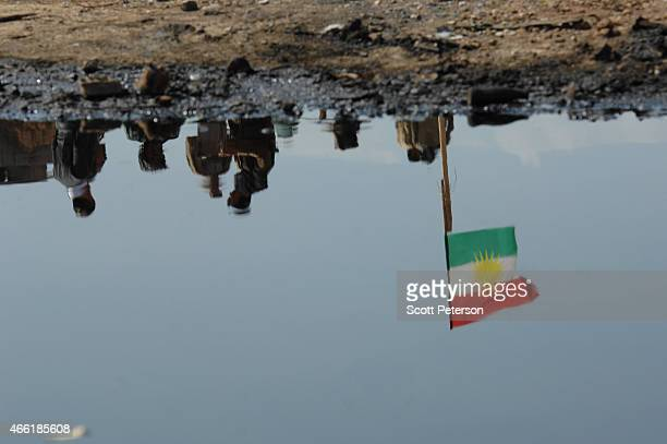 Kurdish flag at apeshmerga checkpoint is reflected in pools of oil with damaged oil pipeline infrastructure as Iraqi Kurdish forces push the...