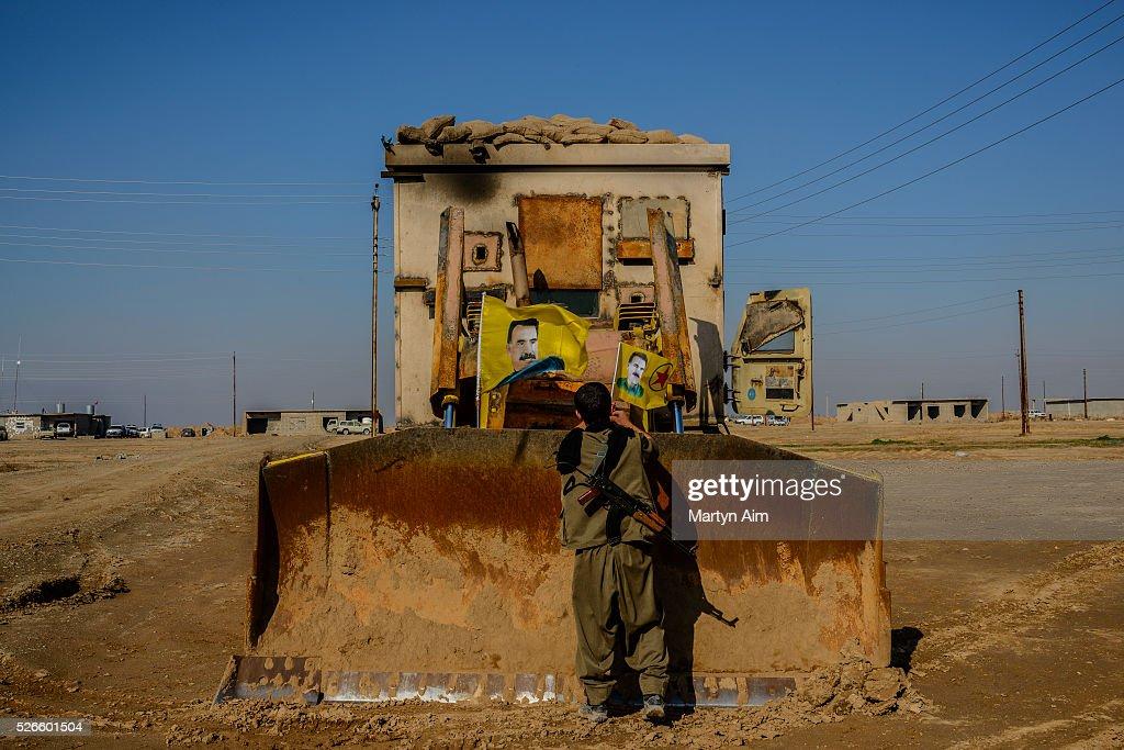 A Kurdish HPG Star fighter places flags of Abdullah Ocalan a founding member of the PKK on an armoured bulldozer at Matara Base in Kirkuk province...