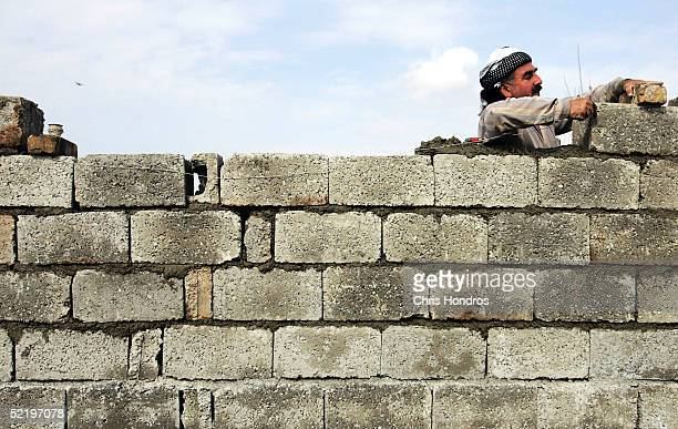 Kurdish laborer builds the wall of a house February 13 2005 in Kirkuk Iraq Home building is booming in the city among Kurds as Kurdish officials have...