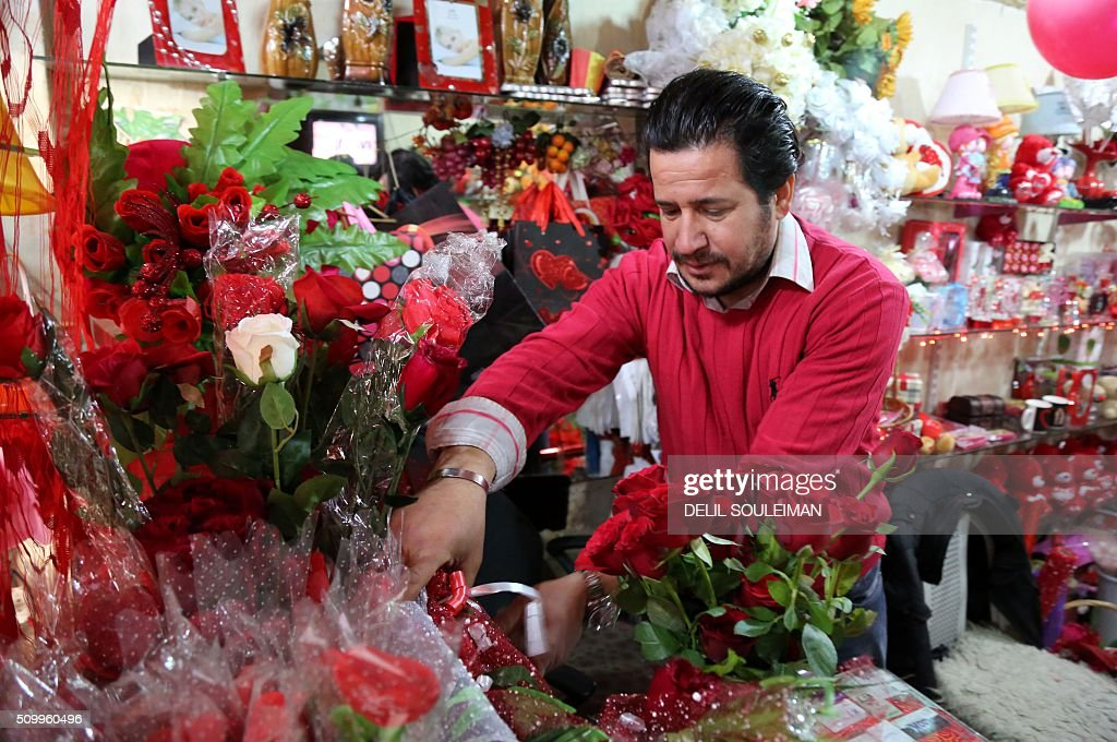 A Kurdish man arranges flowers at his shop ahead of Valentine's day, in the northeastern Syrian city of Qamishli on February 13, 2016. / AFP / DELIL SOULEIMAN