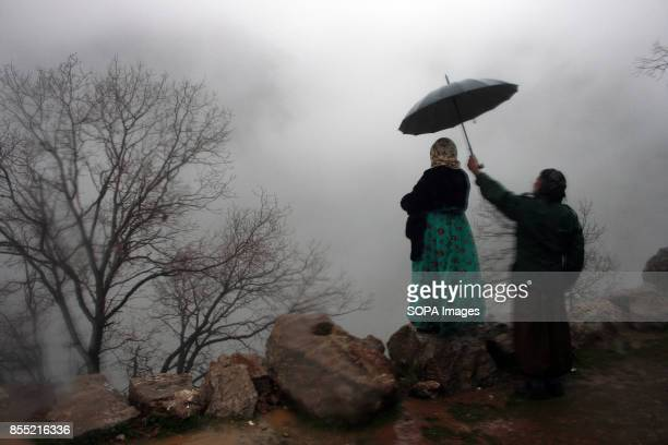 Kurdish man holds an umbrella for his wife during the rain Every year in the Kurdish village of Uraman Takht in west Iran the locals celebrate the...