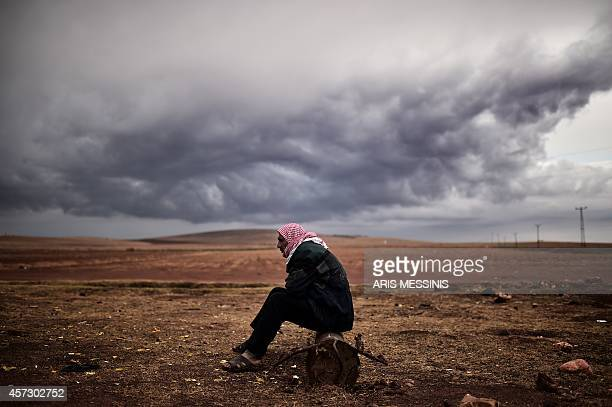A Kurdish man sits at the border area close to the southeastern village of Mursitpinar in the Sanliurfa province opposite the Syrian town of Kobane...