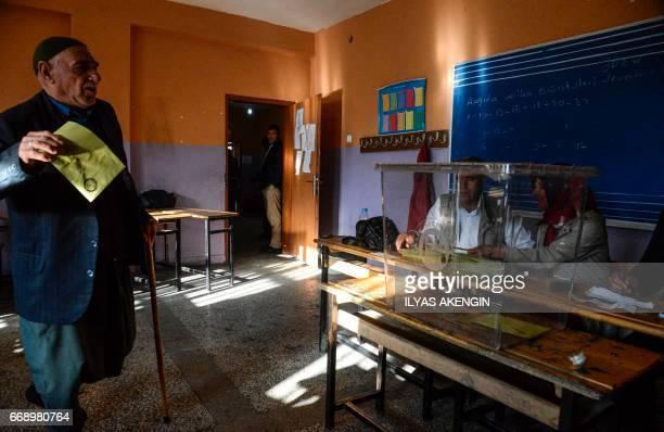 A Kurdish man votes in Turkey's tightlycontested referendum on expanding the powers of President Recep Tayyip Erdogan April 16 2017 in the center of...