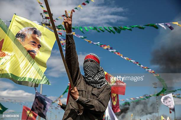 Kurdish man wearing a mask flashes the vsign as he holds up a flag with a picture of the jailed PKK leader Abdullah Ocalan during Newroz celebrations...