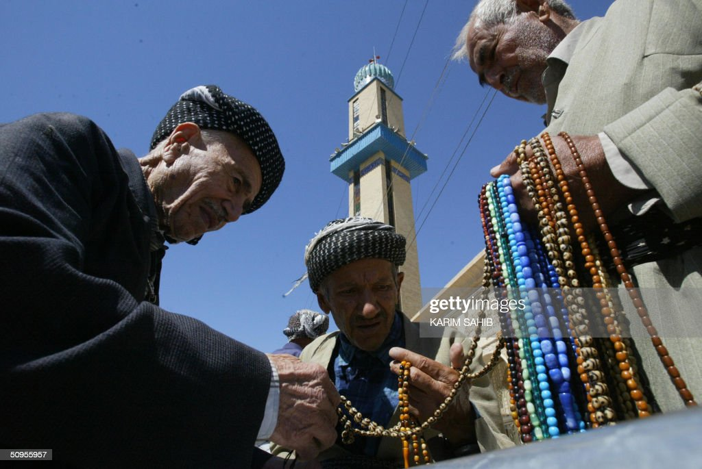 Kurdish men look at prayer beads being sold outside the Suleimaniya Mosque in the northern Kurdish city of Suleimaniya 330 kms from Baghdad 13 June...