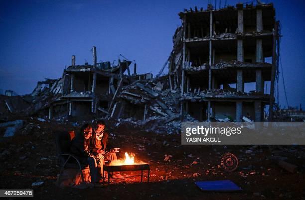 Kurdish men sit near bonfire near a destroyed building in the Syrian Kurdish town of Kobane also known as Ain alArab on March 22 2015 AFP PHOTO/YASIN...