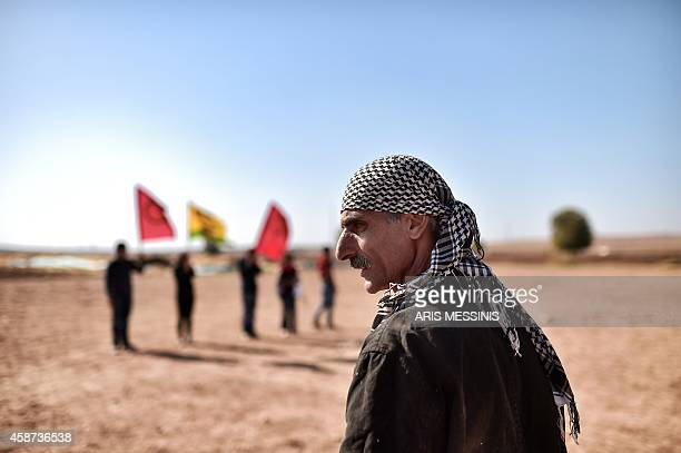 Kurdish people demonstrate in the southeastern border village of Mursitpinar Sanliurfa province on November 10 near the Syrian town of Kobane also...