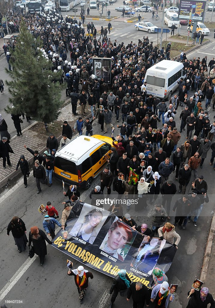 Kurdish people hold a banner reading 'Our three comrades are immortal' and bearing the portraits of the slain members of the Kurdistan Workers' Party (PKK), Sakine Cansiz, Leyla Soylemez, and Fidan Dogan, during a protest in Diyarbakir against the killings of the three Kurdish women activists, in Diyarbakir, on January 13, 2013. Turkish Prime Minister Recep Tayyip Erdogan called on France on January 12 to 'immediately' clarify the killing of three Kurdish activists who were shot dead in Paris, while asking French President Francois Hollande to explain why he was meeting with members of the outlawed PKK.