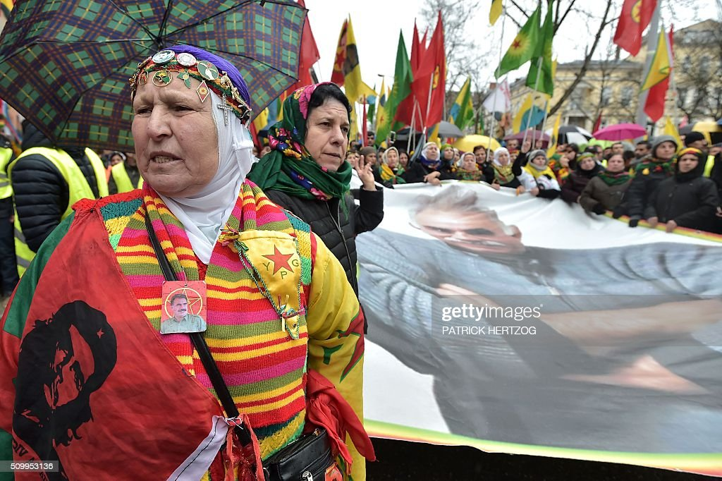 Kurdish people hold a huge picture of jailed leader of Turkey's Kurd rebels, Abdullah Ocalan, in Strasbourg, eastern France, on February 13, 2016, during the annual rally of Kurds from all over Europe to denounce the detention of Abdullah Ocalan. Ocalan was captured by Turkish undercover agents in Kenya in 1999, brought back to Turkey and sentenced to death. His sentence was later commuted to life. / AFP / PATRICK HERTZOG