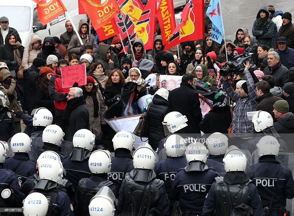 Kurdish people hold photos of the three killed Kurdish activists, Sakine Cansiz, Fidan Dogan and Leyla Soylemez during a demonstration in Ankara on January 10, 2015. The three women were shot dead on January 9, 2013 at the Kurdish Information Centre in Paris. The motives of the triple killing remain unclear. AFP PHOTO/ADEM ALTAN