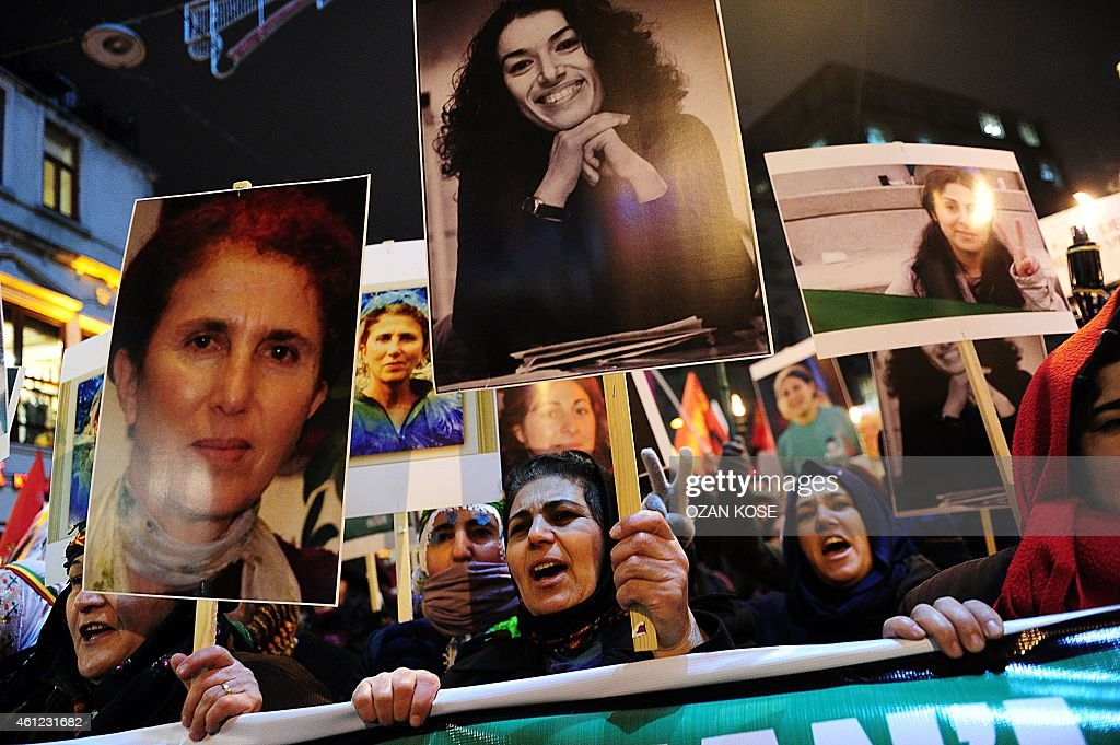 Kurdish people hold pictures of killed three kurdish activists and shout slogans during a demonstration on January 9, 2015 at Istiklal avenue in Istanbul to commemorate the killing of the three top Kurdish activists Sakine Cansiz, Fidan Dogan and Leyla Soylemez. The three women were shot to death on January 9, 2013 at the Kurdish Information Centre in Paris. The motives of the triple killing remain unclear. Banner reads: '365 days later, we are still waiting for the truth. Find those responsible'. AFP PHOTO/OZAN KOSE