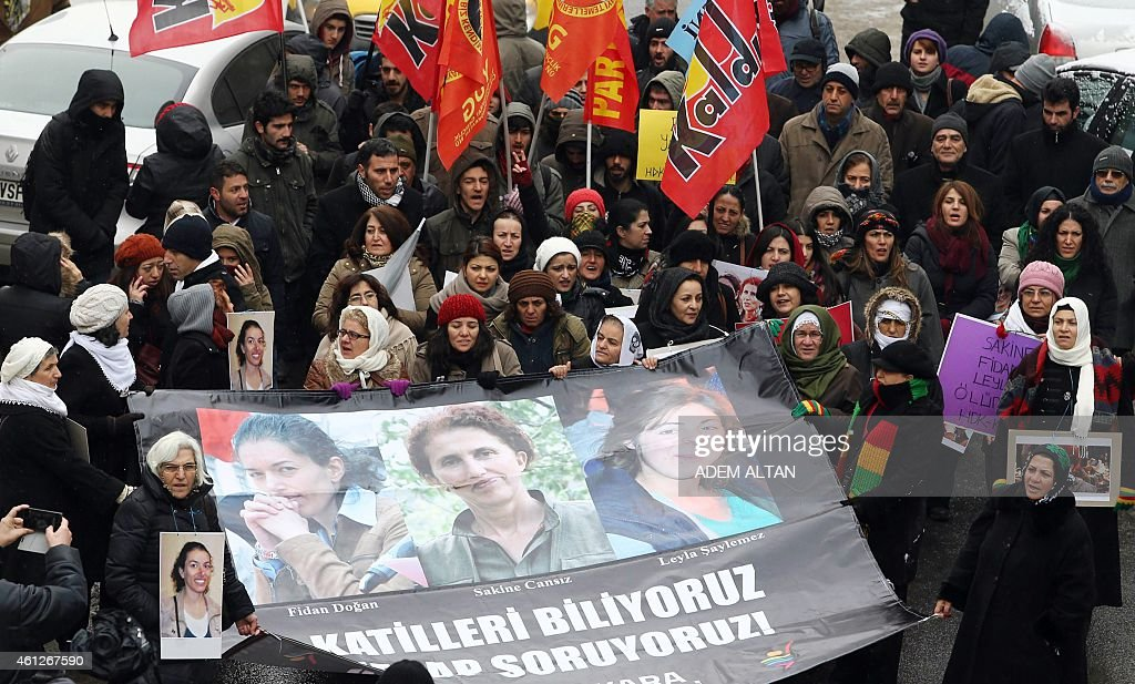 Kurdish people stand behind a banner reading 'We know the killers, we want them to be accountable' and bearing photos of the three killed kurdish activists, <a gi-track='captionPersonalityLinkClicked' href=/galleries/search?phrase=Sakine+Cansiz&family=editorial&specificpeople=10112049 ng-click='$event.stopPropagation()'>Sakine Cansiz</a>, Fidan Dogan and Leyla Soylemez during a demonstration in Ankara on January 10, 2015. The three women were shot dead on January 9, 2013 at the Kurdish Information Centre in Paris. The motives of the triple killing remain unclear. AFP PHOTO/ADEM ALTAN
