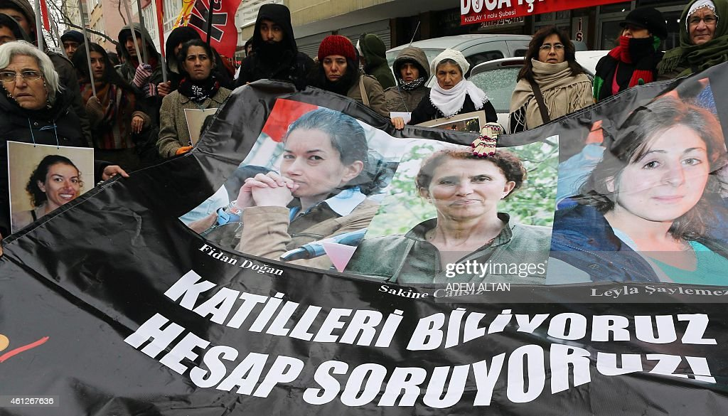 Kurdish people stand behind a banner reading 'We know the killers, we want them to be accountable' and bearing photos of the three killed kurdish activists, Sakine Cansiz, Fidan Dogan and Leyla Soylemez during a demonstration in Ankara on January 10, 2015. The three women were shot dead on January 9, 2013 at the Kurdish Information Centre in Paris. The motives of the triple killing remain unclear. AFP PHOTO/ADEM ALTAN