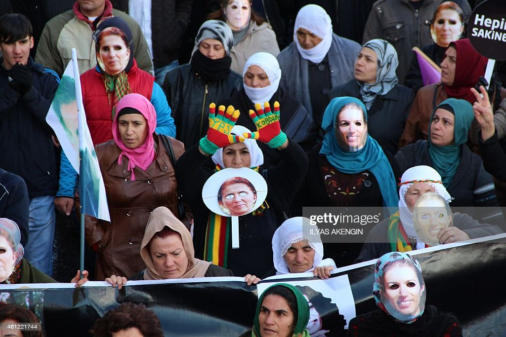 Kurdish people take part in a demonstration on January 9, 2015 in Diyarbakir to commemorate the killing of the three top Kurdish activists Sakine Cansiz, Fidan Dogan and Leyla Soylemez. The three women were shot to death on January 9, 2013 at the Kurdish Information Centre in Paris. The motives of the triple killing remain unclear. Banner reads: '365 days later, we are still waiting for the truth. Find those responsible!'. AFP PHOTO/ILYAS AKENGIN