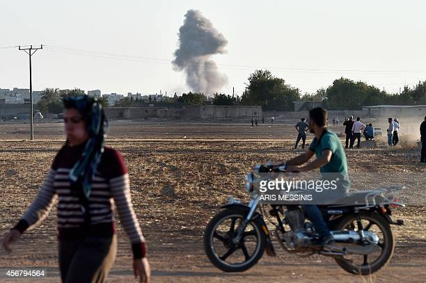 Kurdish people wach air strikes at the Syrian town of Ain alArab known as Kobane by the Kurds as seen from the TurkishSyrian border during heavy...
