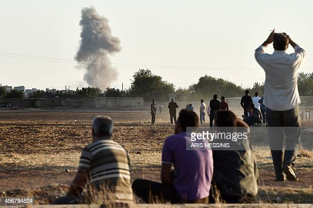 Kurdish people watch air strikes at the Syrian town of Ain alArab known as Kobane by the Kurds as seen from the TurkishSyrian border during heavy...