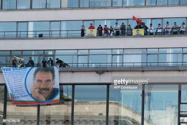 TOPSHOT Kurdish people wave flags and banners picturing jailed Kurdish leader Abdullah Ocalan as they take part in a demonstration on the balconies...