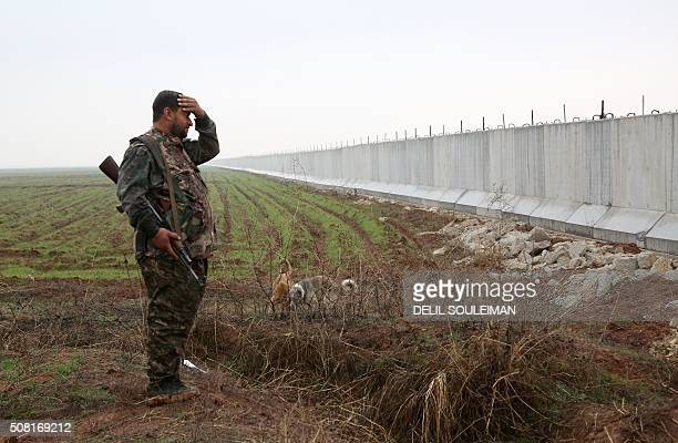 A Kurdish People's Protection Unit fighter stands near a wall which activists say was put up by Turkish authorities on the SyriaTurkey border in the...